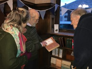 "Iona, Diarmid and Robin with a copy of the ""Lives of the Lindsays"" showing the Library book-plate. – photo by Lady Balniel."